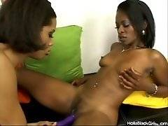 Pretty ebony sweetie is turning herself on by rubbing nipples while other babe fucks her wet pussy with toy.